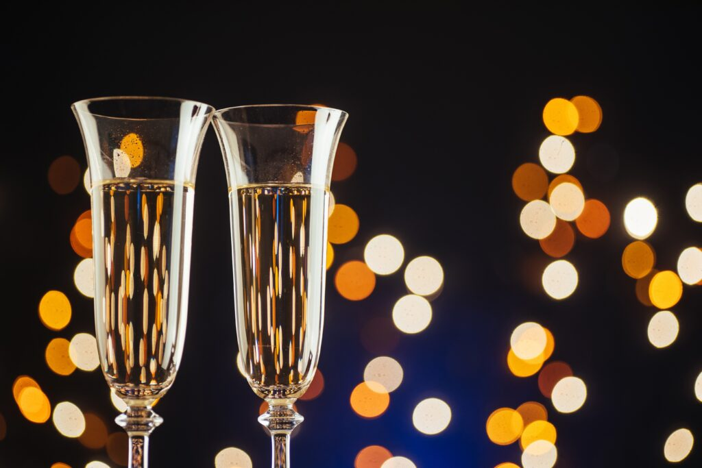 Champagne for festive occasions against a dark background with gold shimmering light and bokeh
