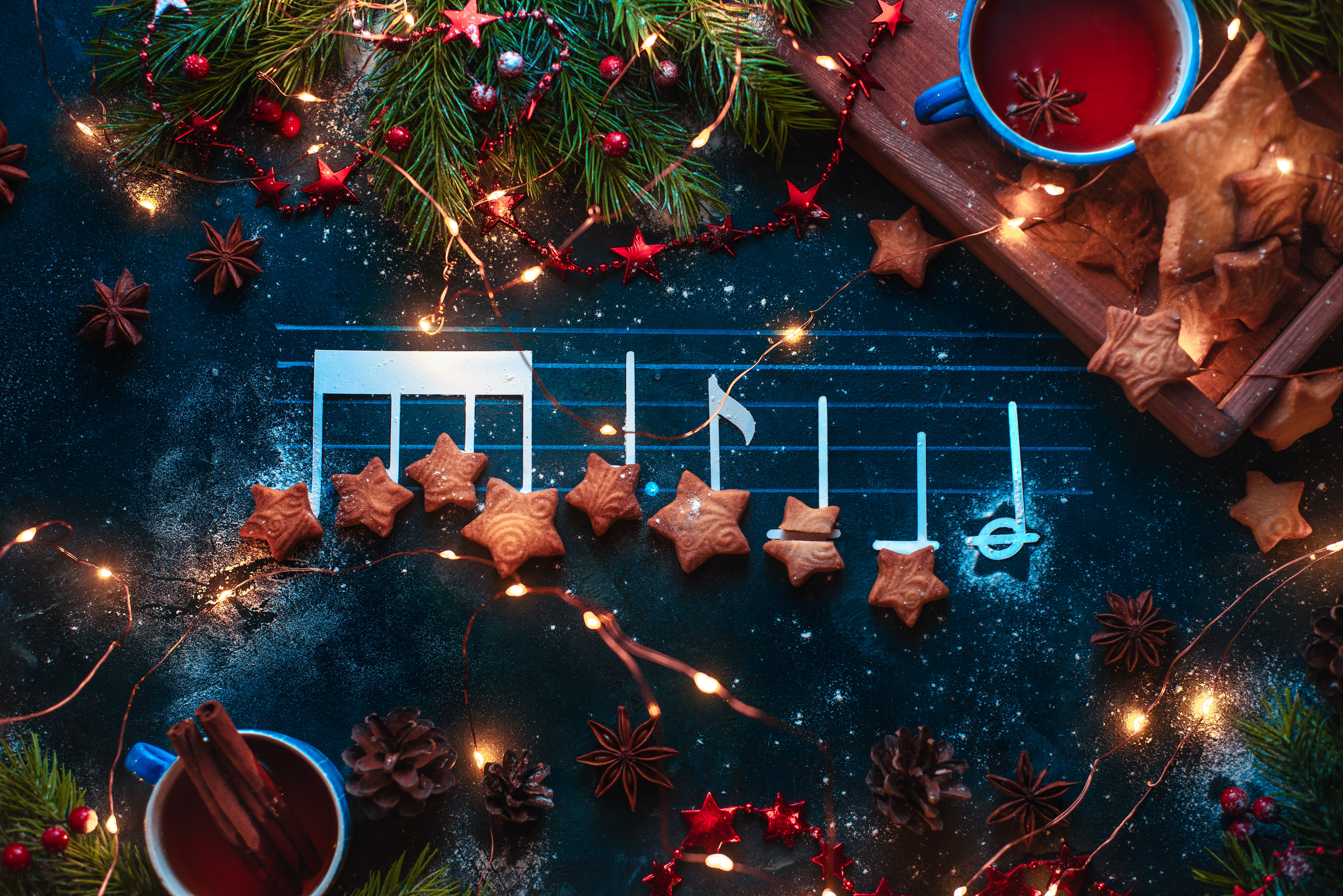 Christmas melody notes flat lay with star-shaped cookies, fir tree branches, wooden tray, anise stars, and decorations. Christmas carol concept for a header or postcard