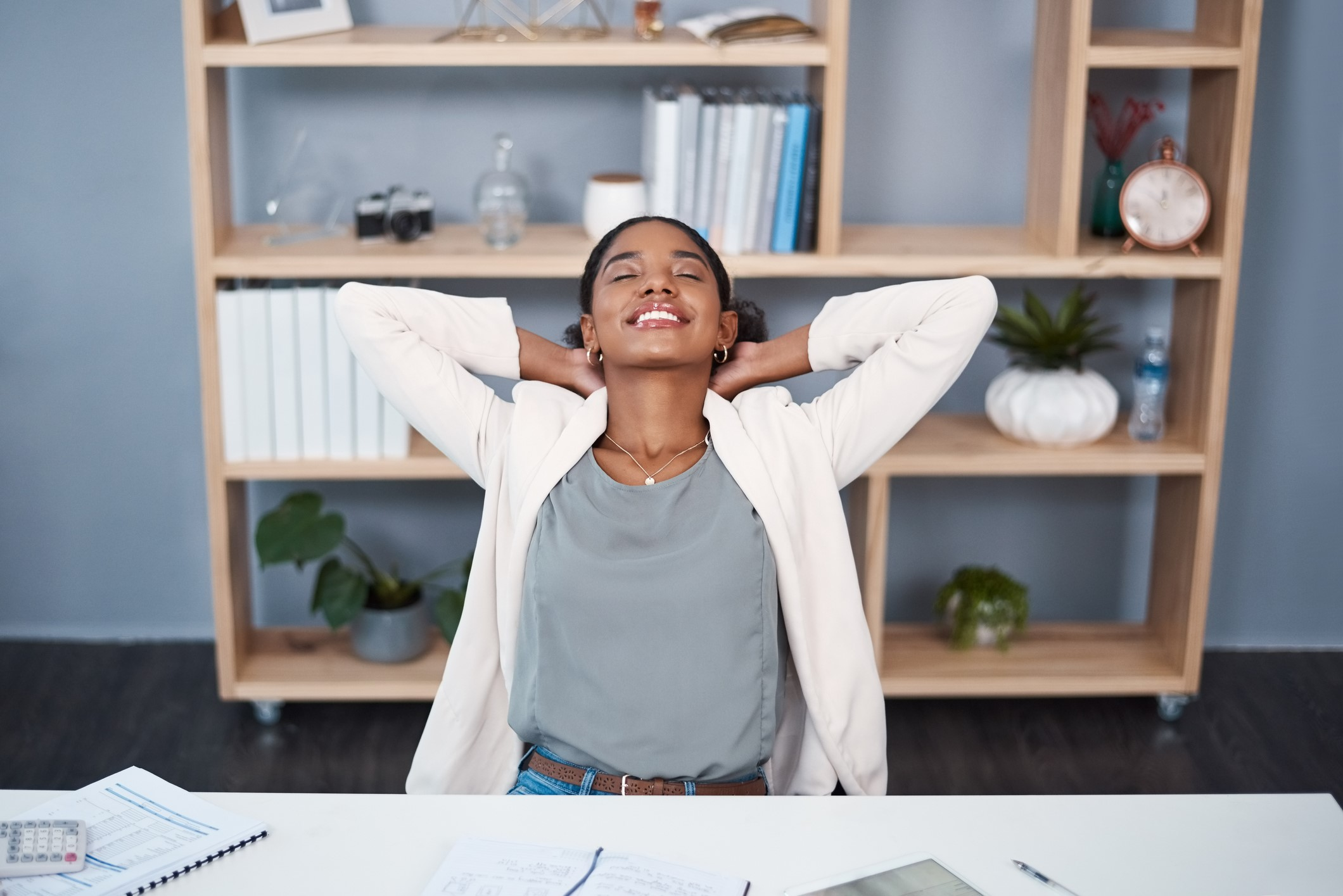Shot of a young businesswoman relaxing at her desk in a modern office