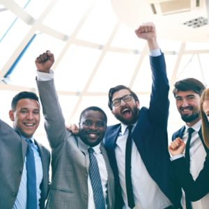 A group of people in business attire raising their fists in the air.