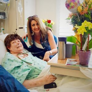 A woman visiting another woman in the hospital.