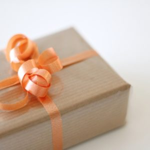 A present with tan wrapping paper and orange curly ribbon.