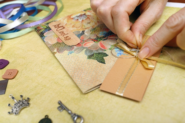 A pair of hands tying a ribbon on a small greeting card.