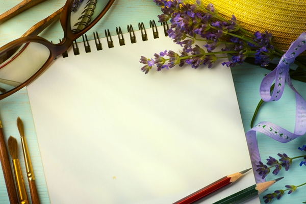 A desk scene with a notebook, a few pencils and lilac.